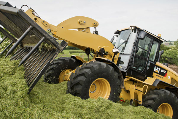 Cat Wheel Loader with Rake Attachment on Pile of Hay